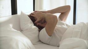 Jeune femme sur le bâti au matin Homme dormant dans le lit avec l'alarme de téléphone banque de vidéos
