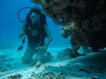 Jeune femme sur le fond sous-marin essayant de tapoter une petite pente tandis que Di Photo stock