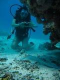 Jeune femme sur le fond sous-marin montrant le signal d'amour à une petite pente Photographie stock libre de droits