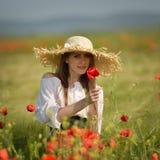 Jeune femme sur le gisement de céréale avec des pavots en été Images stock