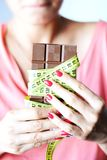 Jeune femme sur le régime tenant un chocolat avec la bande jaune de mesure enroulée autour de elle Image libre de droits