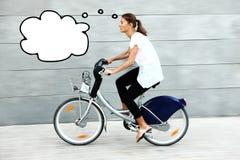 Jeune femme sur penser de vélo Photo stock