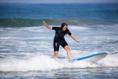 Jeune femme sur sa planche de surf Photographie stock libre de droits
