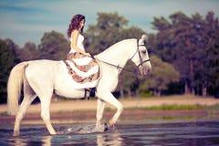 Jeune femme sur un cheval Cavalier de horseback, cheval d'équitation de femme sur b image libre de droits