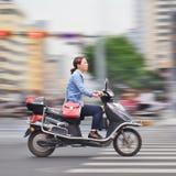 Jeune femme sur un e-vélo rapide, Kunming, Chine Images stock