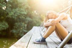 Jeune femme sur un pont en bois dans des espadrilles de jeans Photos libres de droits