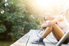Jeune femme sur un pont en bois dans des espadrilles de jeans Photographie stock libre de droits