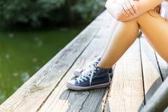 Jeune femme sur un pont en bois dans des espadrilles de jeans Photo libre de droits