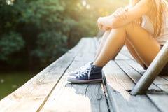 Jeune femme sur un pont en bois dans des espadrilles de jeans Image libre de droits