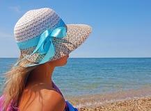 Jeune femme sur une plage dans un chapeau de paille Images libres de droits