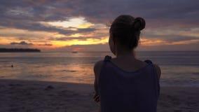 Jeune femme sur une plage observant un coucher du soleil fantastique banque de vidéos