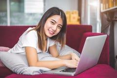 Jeune femme surfant l'Internet par l'ordinateur portable sur le sofa rouge dans le cheerf photos stock