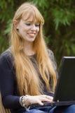 Jeune femme tapant sur un ordinateur portatif Photographie stock libre de droits