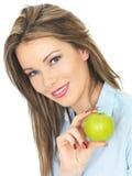 Jeune femme tenant Apple vert juteux mûr Image libre de droits