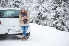 Jeune femme tenant après la voiture sur un fond de forêt couverte de neige d'hiver Photos stock