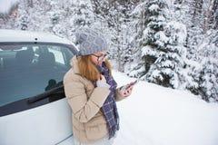 Jeune femme tenant après la voiture sur un fond de forêt couverte de neige d'hiver Image libre de droits