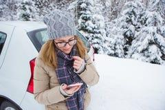 Jeune femme tenant après la voiture sur un fond de forêt couverte de neige d'hiver Photo libre de droits