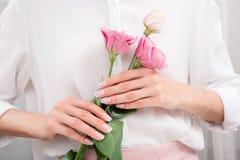 Jeune femme tenant de belles fleurs d'eustoma dans des mains images stock