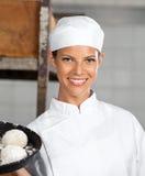Jeune femme tenant des boules de la pâte dans le plateau de cuisson Images stock