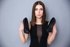 Jeune femme tenant des chaussures au-dessus de fond gris Photographie stock libre de droits