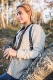 Jeune femme tenant des jumelles au coucher du soleil image libre de droits