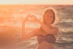 Jeune femme tenant des mains dans la forme de coeur Sun et océan au b Photo libre de droits