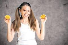 Jeune femme tenant des oranges Photo stock