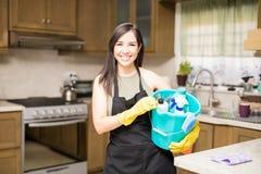 Jeune femme tenant des outils et des produits de nettoyage dans le seau photographie stock libre de droits