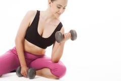 Jeune femme tenant des poids et faisant la forme physique images stock