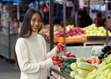 Jeune femme tenant des tomates au marché végétal Images stock