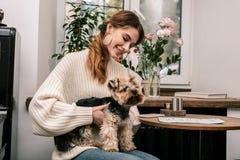 Jeune femme tenant heureusement son petit chien images stock