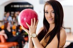 Jeune femme tenant la boule rose dans le club de bowling Photo stock
