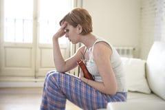 Jeune femme tenant la bouteille d'eau chaude dans la crampe d'estomac de ventre et la douleur de souffrance de période photographie stock