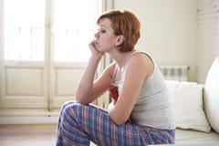 Jeune femme tenant la bouteille d'eau chaude dans la crampe d'estomac de ventre et la douleur de souffrance de période photo stock