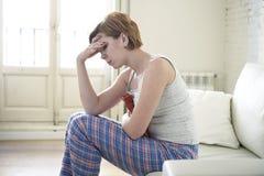 Jeune femme tenant la bouteille d'eau chaude dans la crampe d'estomac de ventre et la douleur de souffrance de période images libres de droits