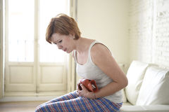 Jeune femme tenant la bouteille d'eau chaude dans la crampe d'estomac de ventre et la douleur de souffrance de période image libre de droits