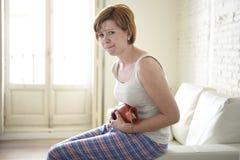 Jeune femme tenant la bouteille d'eau chaude dans la crampe d'estomac de ventre et la douleur de souffrance de période photographie stock libre de droits