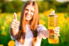Jeune femme tenant la bouteille d'huile dans des pouces de gisement et d'exposition de tournesol  image stock