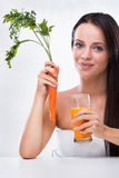 Jeune femme tenant la carotte et le jus de carotte image stock