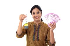 Jeune femme tenant la clé de forme de maison et 2000 notes de roupie Images libres de droits