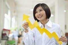 Jeune femme tenant la coupe de papier de signe de flèche Photographie stock