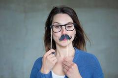 Jeune femme tenant la faux moustache et verres pour faire face images stock