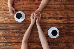 Jeune femme tenant la main de femme agée en café, photo de dessus-vue photographie stock libre de droits