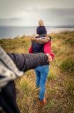 Jeune femme tenant la main de l'homme et menant par a Photographie stock libre de droits