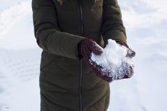 Jeune femme tenant la neige dans des ses mains dans des mitaines, hiver, amusement, joie, sports, récréation, enfants images stock
