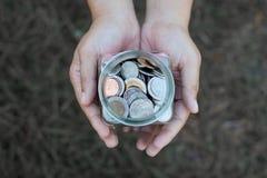 Jeune femme tenant la pièce de monnaie dans la bouteille en verre dans des mains image stock