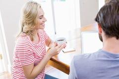 Jeune femme tenant la tasse de café tandis qu'homme à l'aide de l'ordinateur portable Image libre de droits