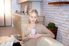 Jeune femme tenant la tasse de thé à la maison image libre de droits
