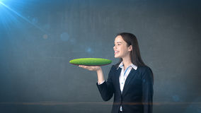 Jeune femme tenant la terre 3D sur la paume ouverte de main avec le copyspace vide, fond d'isolement de studio Concept d'affaires Image libre de droits
