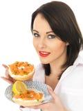 Jeune femme tenant le bagel fumé de fromage de saumon et fondu Photographie stock libre de droits